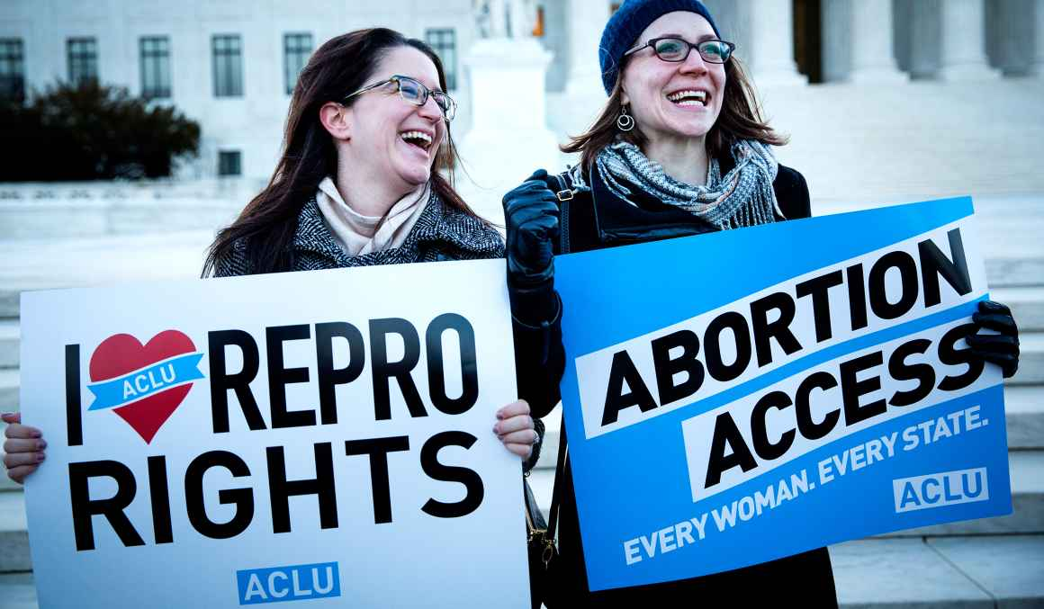 women holding reproductive rights signs outside the Supreme Court