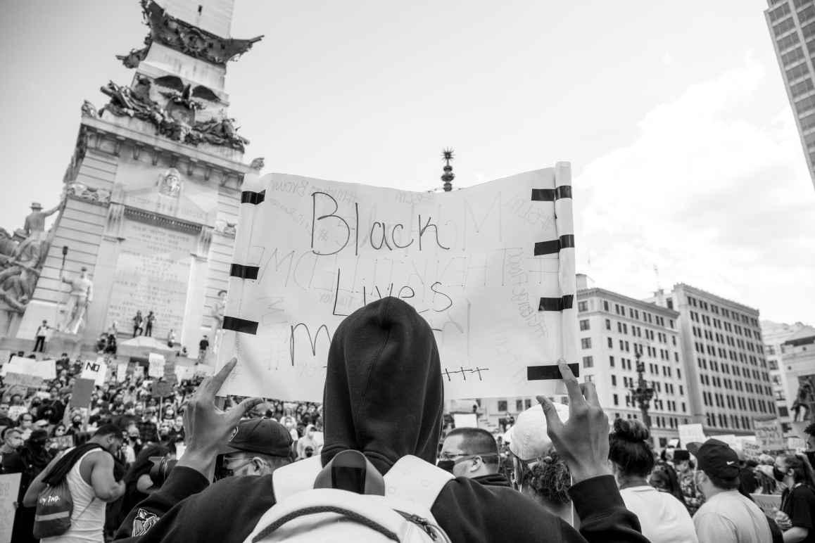 Protester holding black lives matter sign on monument circle
