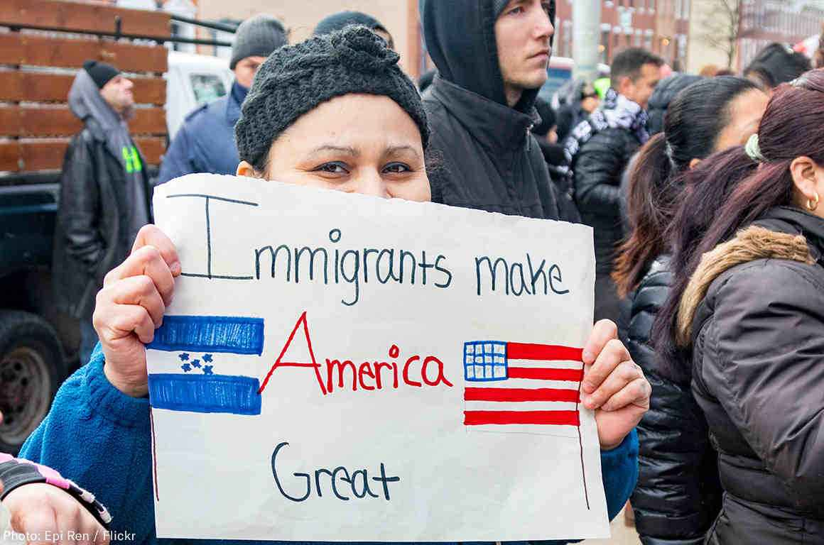 """Young woman with a sign reading """"Immigrants make America great"""""""